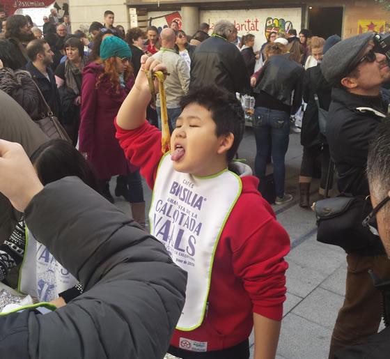Un chico oriental comiendo calçots en la Plaza de la Zeta durante la Fiesta de la Calçotada 2016