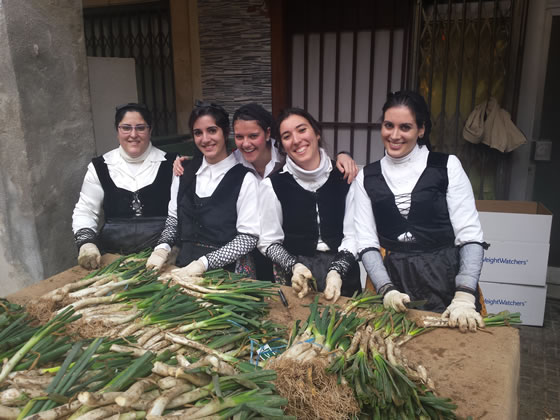El grupo de chicas que cortaban las raíces en la demostración de asar calçots de la Fiesta de la Calçotada 2016