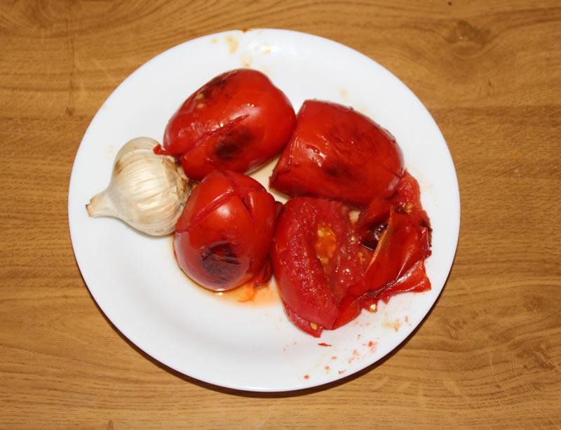 Tomates y ajo ya escalibados en el horno.  Lo ideal sería hacerlo al fuego.